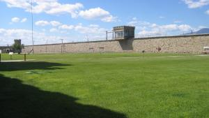 A prison yard with grass, stone walls, and a tower.