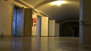 A line of solitary confinement cells with the doors open