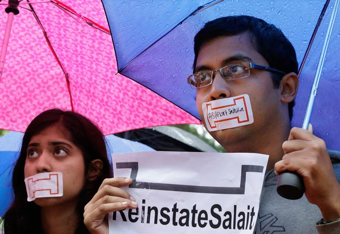 """Students with their mouths taped shut holding a sign that reads """"Reinstate Salaita"""""""