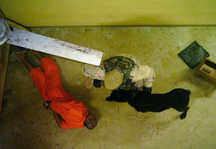 A prisoner with his hands handcuffed behind his back lies on the floor while a guard with a dog stands over him
