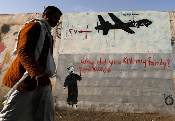"""Man walks past wall with graffiti of a U.S. drone and a small boy writing """"why did you kill my family?"""""""