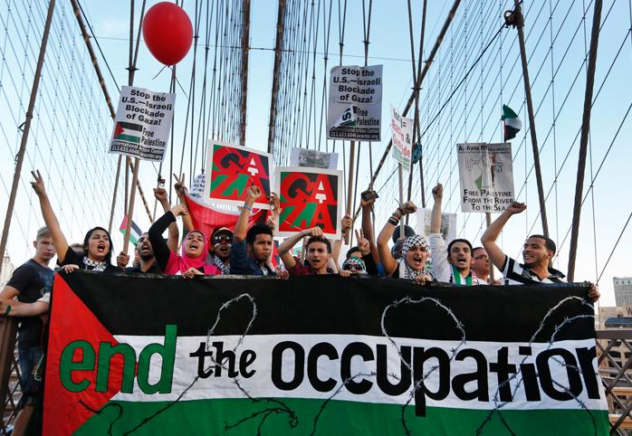 """Protestors march across the Brooklyn Bridge holding a banner that reads """"End the Occupation"""""""