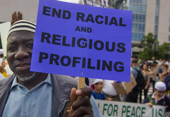 """Protestor holds a sign that says """"End Racial and Religious Profiling"""""""