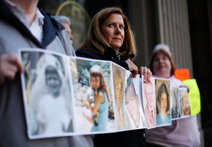 Members of the Survivors Network of those Abused by Priests hold photos of themselves at the age they were sexually assaulted by Catholic Clergy.
